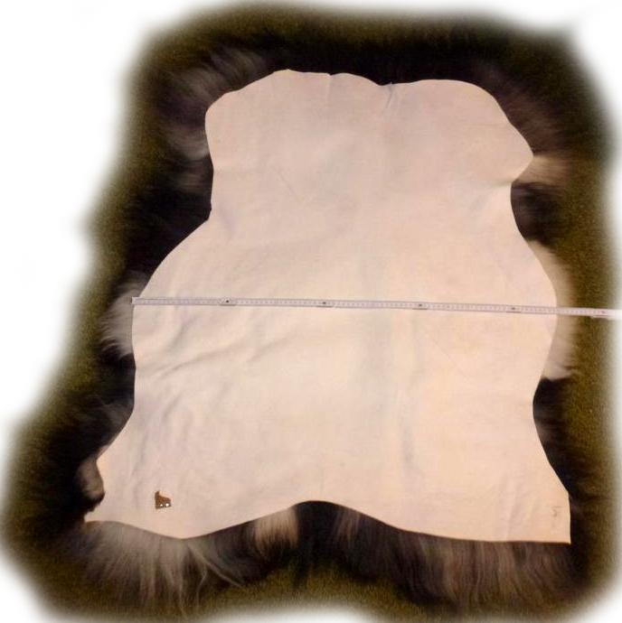 Schwarzes Islandschaffell mit weißen Anteilen am Saum
